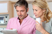 Middle aged couple using tablet in kitchen — Stock Photo