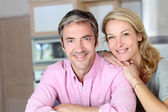 Cheerful couple leaning on kitchen counter — Stock Photo