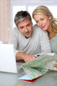 Mature couple planning vacation trip with map and laptop — Stock Photo