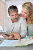 Mature couple planning vacation trip with map and laptop — Stockfoto