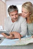 Ouder paar van plan vakantiereis met kaart en een laptop — Stockfoto