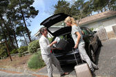 Couple putting suitcases in car trunk for a journey — Stock Photo