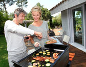 Couple in garden cooking meat on barbecue — Stock Photo