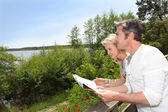 Couple on vacation looking at touristic map — Foto de Stock