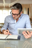 Handsome businessman with eyeglasses working from home — Stock Photo