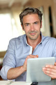 Handsome guy working from home with electronic tablet — Stock Photo