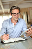 Handsome businessman with eyeglasses working from home — Stockfoto
