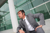 Businessman sitting in stairs in front of building — Stock Photo