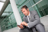 Businessman using mobile phone while seated in stairs — Stock Photo
