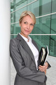 Mature businesswoman standing in front of modern building — Stock Photo