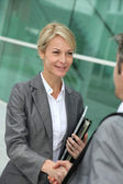 Closeup of sales woman shaking hand to business patner — Stock Photo