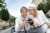 Happy tourists looking at pictures on camera screen — Stock Photo