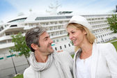 Happy romantic couple standing in front of cruise boat — Stock Photo