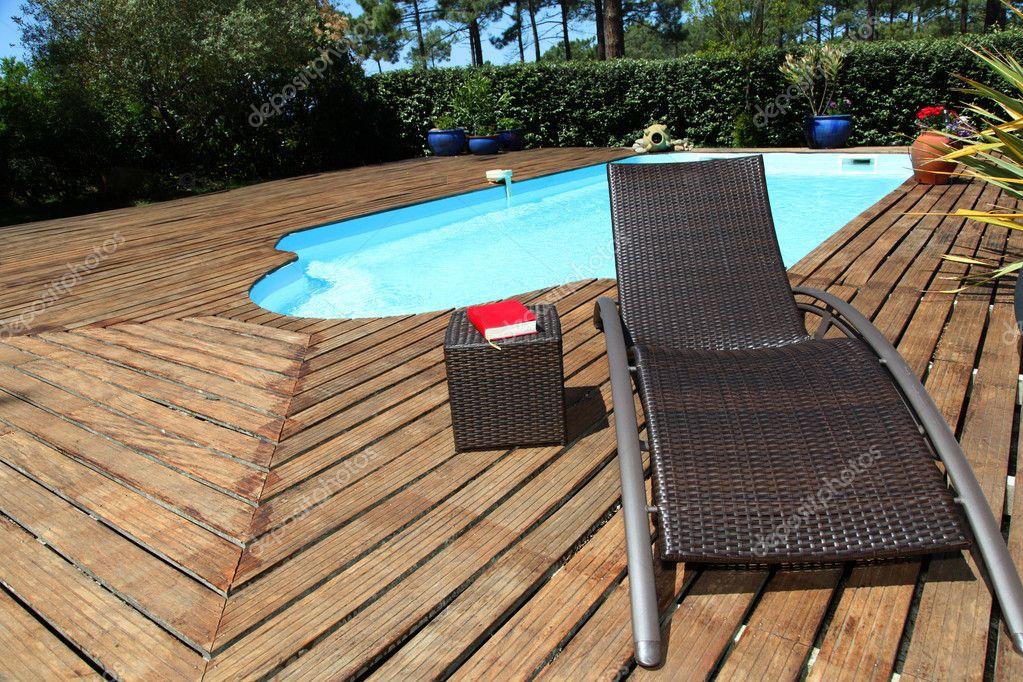 Vista de sillas largas por piscina foto stock goodluz for Sillas de piscina