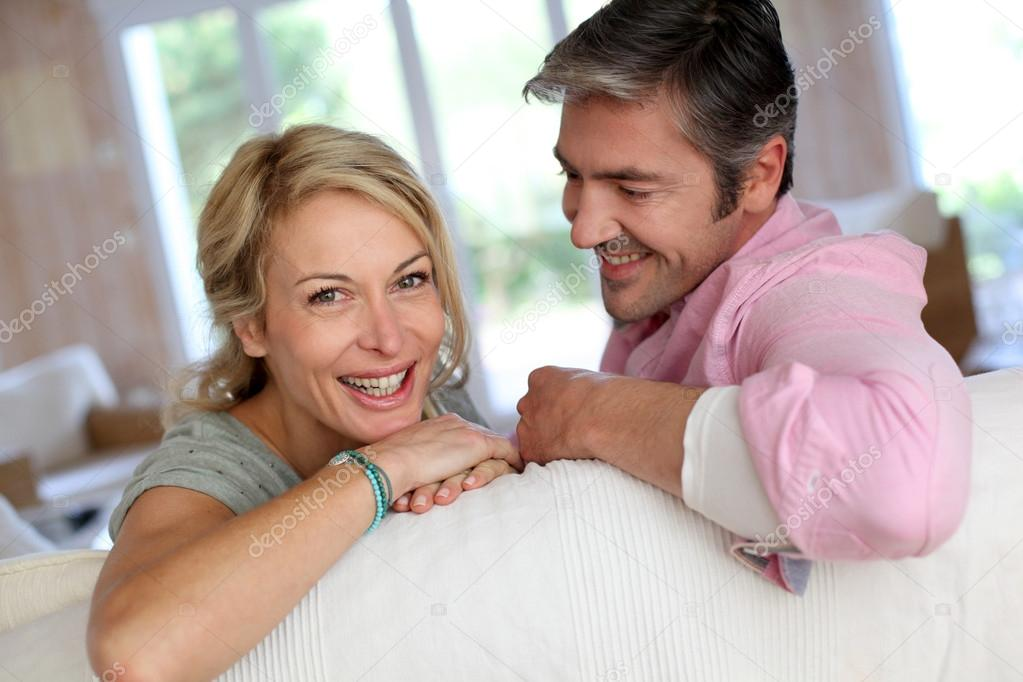 Middle aged couple relaxing in sofa at home  Stock Photo #13942943