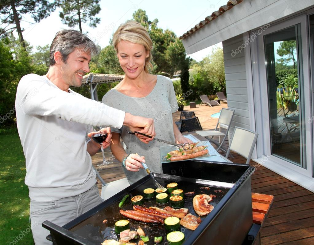 couple in garden cooking meat on barbecue stock photo. Black Bedroom Furniture Sets. Home Design Ideas