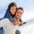 Man giving piggyback ride to girlfriend on the beach — Stock Photo