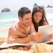 Couple at the beach using electronic tablet — Stock Photo #13956748
