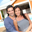 Young couple sitting in front of brand new home — Stock Photo #13956877