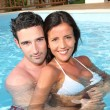 Young smiling couple bathing in private pool — Stock Photo #13956893