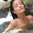 Attractive brunette woman taking a bath in river — Stock Photo #13956908