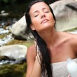 Beautiful young woman applying hair conditioner sitting by river — Stock Photo #13956944