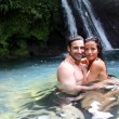 Happy couple bathing near waterfall in island — Stock Photo #13956994