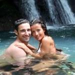 Happy couple bathing near waterfall in island — Stock Photo