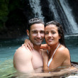 Happy couple bathing near waterfall in island — Stock Photo