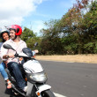 Couple riding motorbike on a country road - Foto Stock
