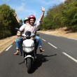 Couple enjoying scooter ride on country road — Stock Photo #13957017