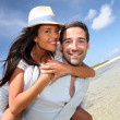 Lovers enjoying sunny day at the beach - Stock Photo