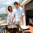 Young couple cooking dinner on barbecue grill — Stock Photo #13957079