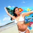 Woman at the beach holding sarong up in the air — Stock Photo