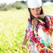 Beautiful gypsy girl with scarf standing in meadow — Stock Photo #13957158