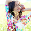 Brunette girl with colorful shirt standing in meadow — Stock Photo