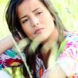 Closeup of beautiful brunette girl sitting in meadow — Stock Photo