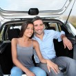 Happy couple sitting in car open trunk — Stock Photo