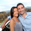 Couple standing by car on the road — Stock Photo #13957232