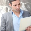 Businessman using electronic tablet outside the office — Stock Photo