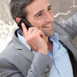 Businessman talking on mobile phone against wall — Stock Photo