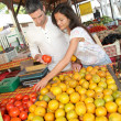 Cheerful couple choosing fruits in outdoor market — Stock Photo #13958969