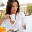 Beautiful woman connected on internet while having breakfast — Stock Photo
