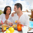 Cheerful couple taking breakfast on the outdoor terrace — Stock Photo