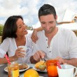 Cheerful couple taking breakfast on outdoor terrace — Stock Photo #13959071