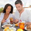 Cheerful couple taking breakfast on the outdoor terrace — Stock Photo