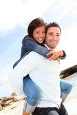Man giving piggyback ride to girlfriend on the beach — Stock Photo