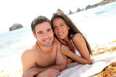 Portrait of romantic couple laying on the beach — Stock Photo