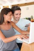 Pareja en casa haciendo compras en línea con el ordenador portátil — Foto de Stock