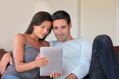 Couple sitting in sofa with electronic tablet — Stock Photo